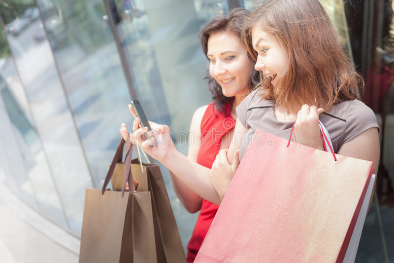 Happy fashion women with bags using mobile phone, shopping center. Happy fashion women with a bags using mobile phone outdoor near the shopping center. At the stock images
