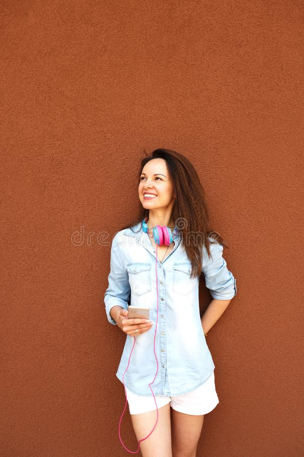 Happy fashionable girl with headphones and a telephone near the wall, smiling and enjoying. Concept of urban style, youth and royalty free stock images