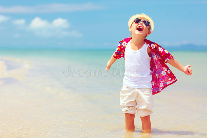 Happy fashionable kid boy enjoys life on summer beach. Happy fashionable kid boy enjoys life on sand beach stock images