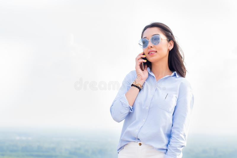 Happy fashionable woman with glasses talking on the phone and smiling at the background of nature, sky. Business lady is successfu stock images