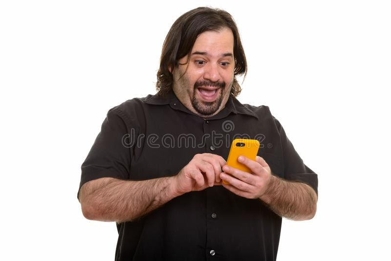 Happy fat Caucasian man laughing while using mobile phone stock photo