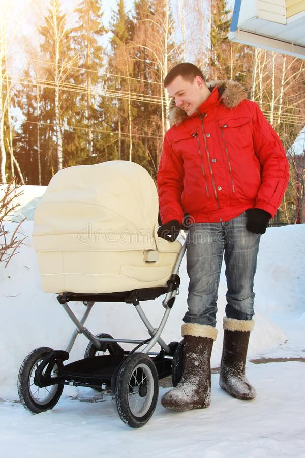 happy father admires baby sleeping in stroller next to him in backyard with snowdrifts in background on winter sunny day stock photo