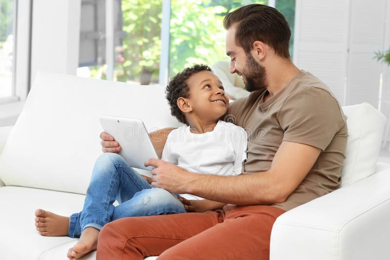 Happy father with adopted African-American boy stock images