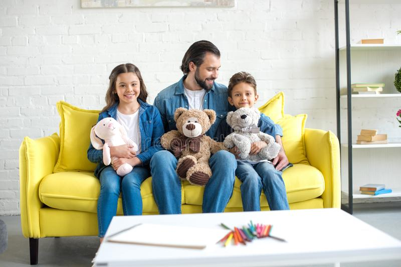Happy father with adorable little kids holding toys and sitting on sofa. At home stock image