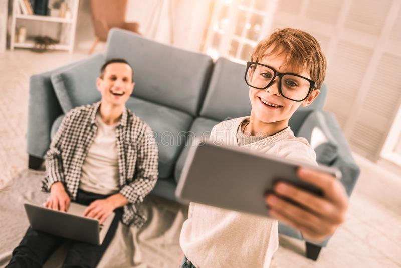 Happy father amused by his son`s goofy behaviour. royalty free stock images