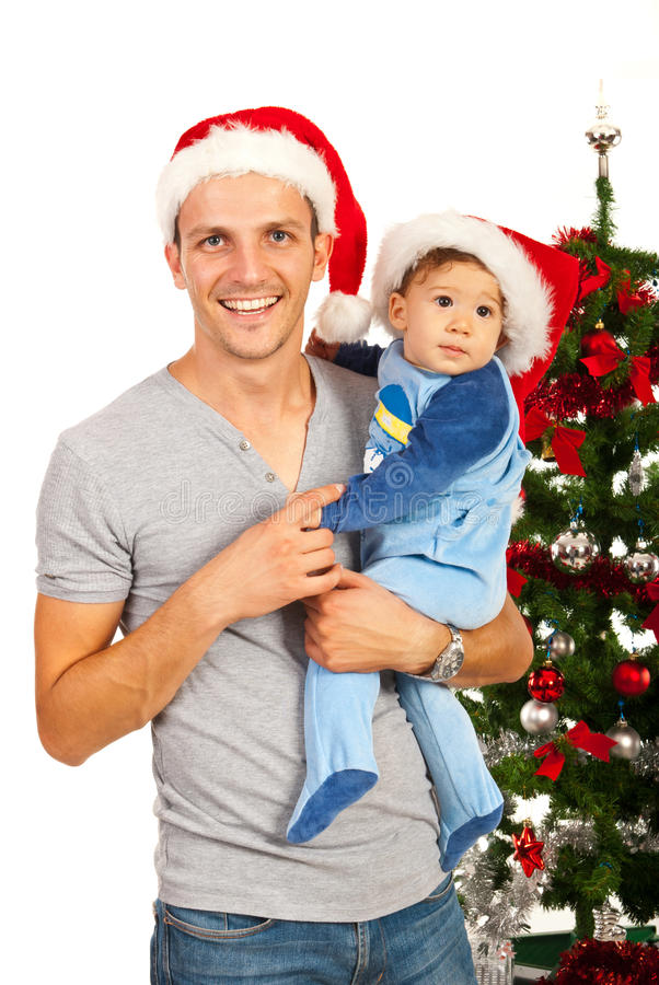 Happy father with baby at Christmas. Happy father with baby boy in front of Christmas tree stock photos