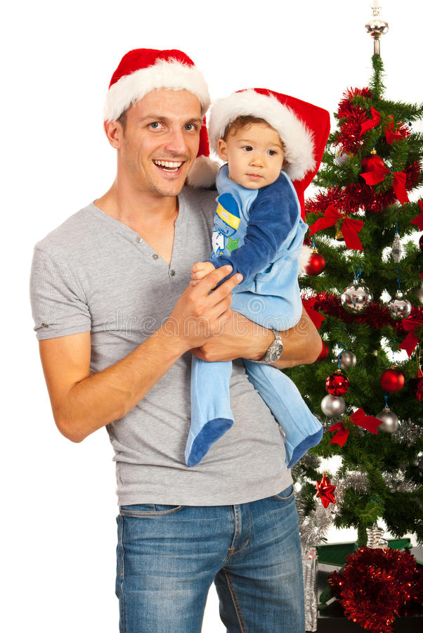 Happy father and baby at first Christmas. Happy father and baby son celebrate first Christmas together in front of tree stock photos