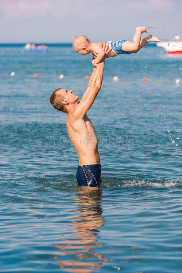 Happy father and baby having fun in the sea. Exercising in whater stock images