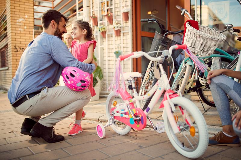 Happy father buys smiling daughter new bicycle in shop. Happy father buys smiling daughter new bicycle in bike shop royalty free stock images