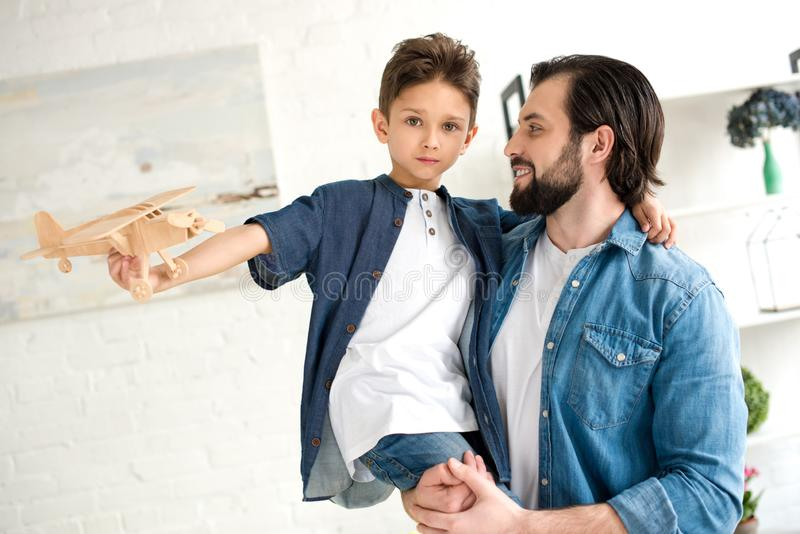 happy father carrying adorable little son playing with toy plane and looking at camera royalty free stock photo