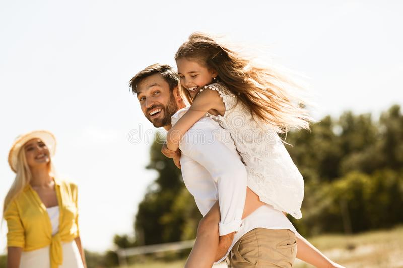 Happy father carrying his daughter on back outdoors royalty free stock photo