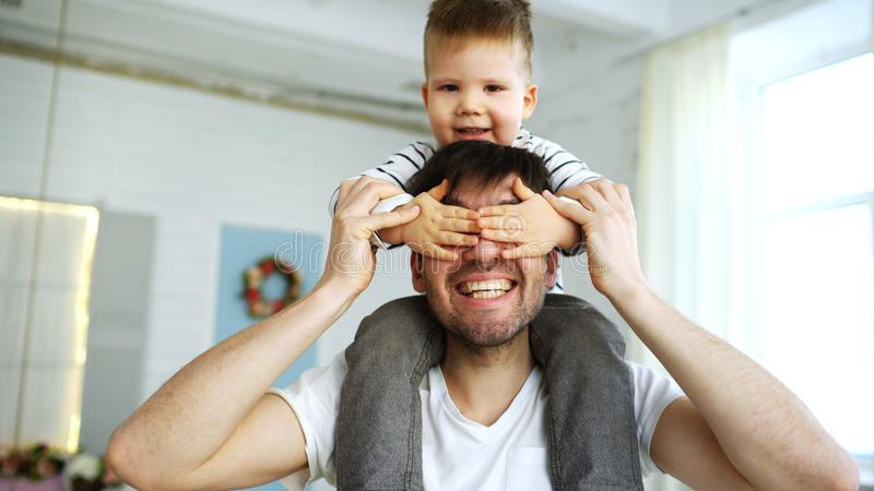 Happy father carrying his smiling son on neck in bedroom. Ath home royalty free stock photography