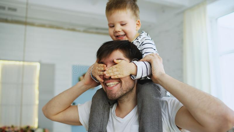 Happy father carrying his smiling son on neck in bedroom. Ath home stock photos