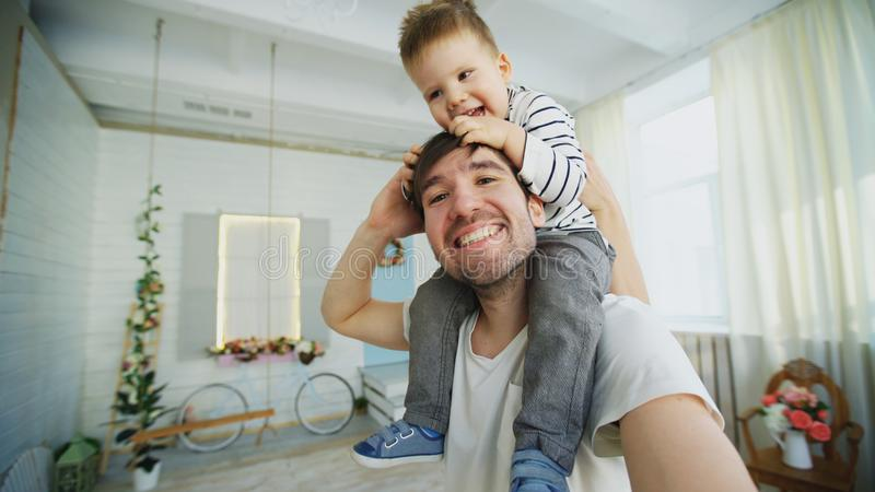 Happy father carrying his smiling son on neck and making selfie on smartphone in bedroom. Ath home stock photos