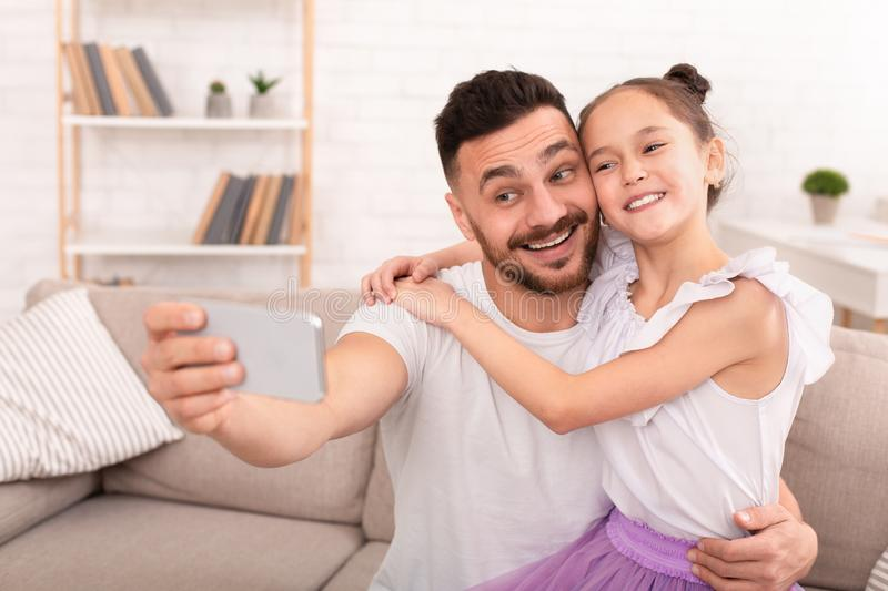 Happy father and child making selfie on cellphone stock image
