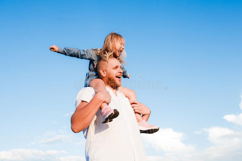 Happy father and child spending time outdoors. Beautiful blonde daughter. royalty free stock images