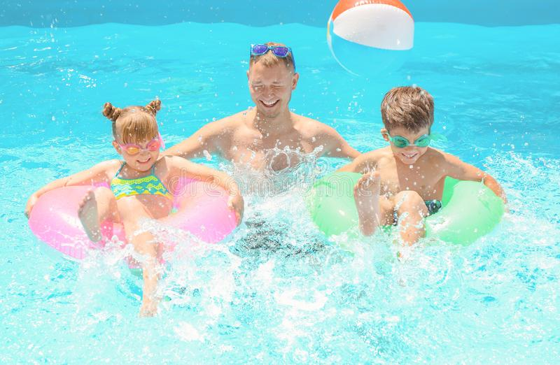 Happy father and children with inflatable rings in swimming pool royalty free stock photos