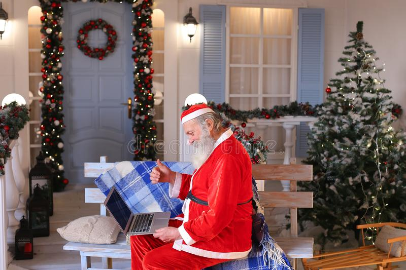Funny Santa Claus showing thumbs up and working with laptop. Happy Father Christmas using approving gestures and enjoying with laptop. Cozy room with stock photos