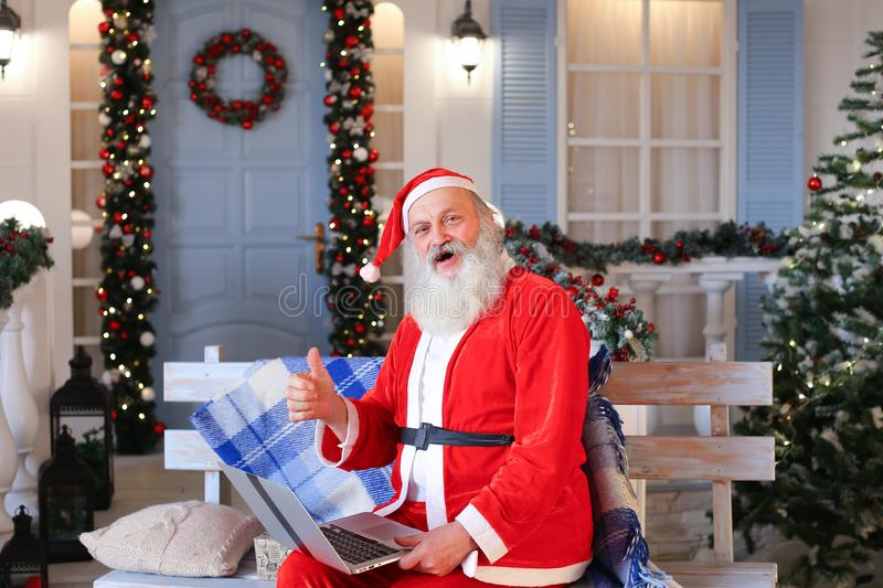 Funny Santa Claus showing thumbs up and working with laptop. Happy Father Christmas using approving gestures and enjoying with laptop. Cozy room with royalty free stock photography
