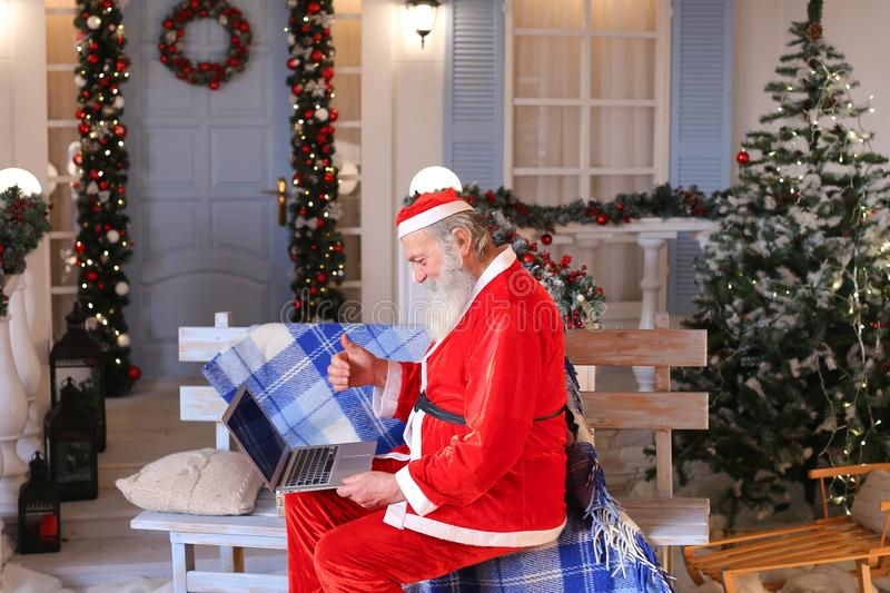 Funny Santa Claus showing thumbs up and working with laptop. Happy Father Christmas using approving gestures and enjoying with laptop. Cozy room with stock photography
