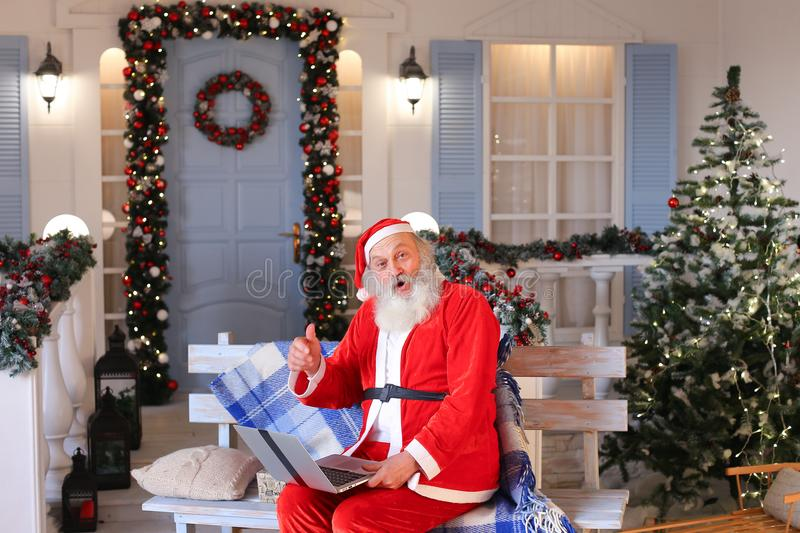 Funny Santa Claus showing thumbs up and working with laptop. Happy Father Christmas using approving gestures and enjoying with laptop. Cozy room with royalty free stock photo