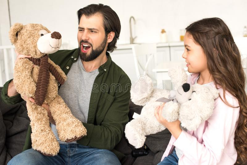 Happy father and cute little daughter playing with teddy bears at home stock photo