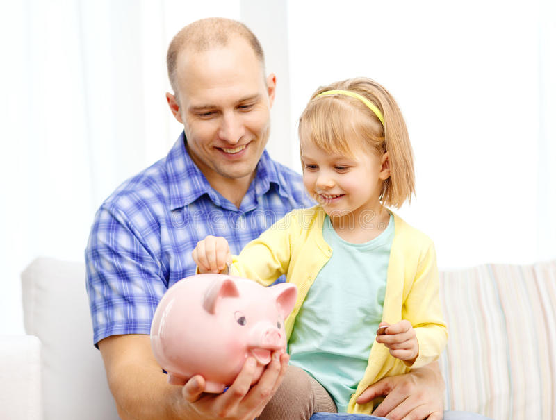 Happy father and daughter with big piggy bank. Family, children, money, investmen and happy people concept - happy father and daughter with big pink piggy bank royalty free stock photo