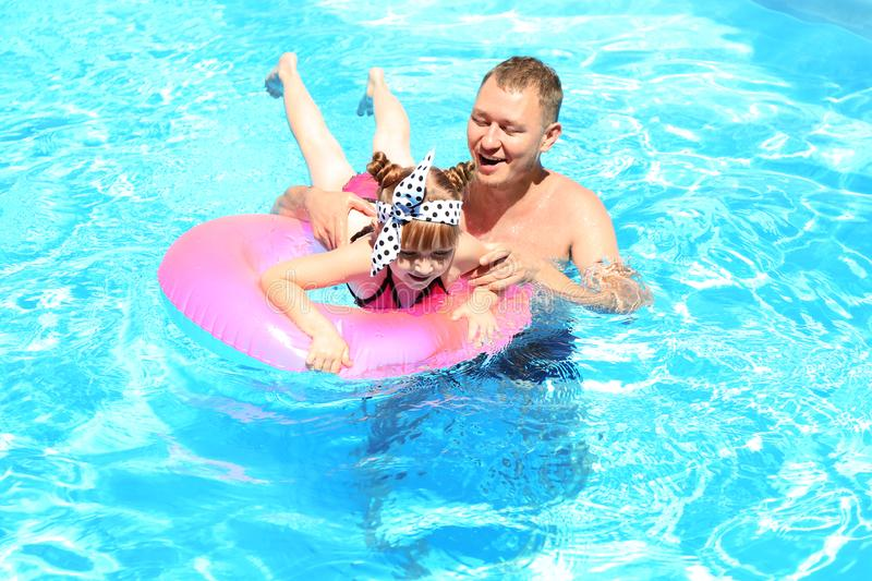 Happy father and daughter with inflatable ring in swimming pool royalty free stock image