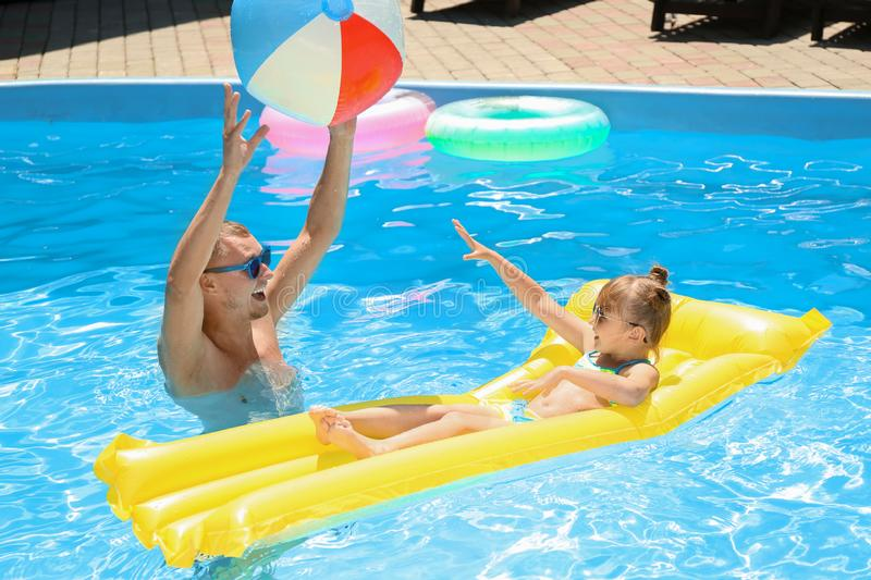 Happy father with daughter playing with ball in swimming pool royalty free stock image