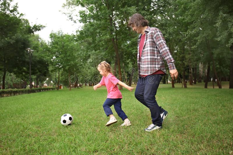 Happy father with daughter playing football in park on summer day royalty free stock photos