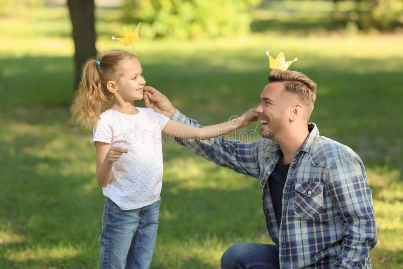 Happy father and daughter playing with party decor in green park royalty free stock images