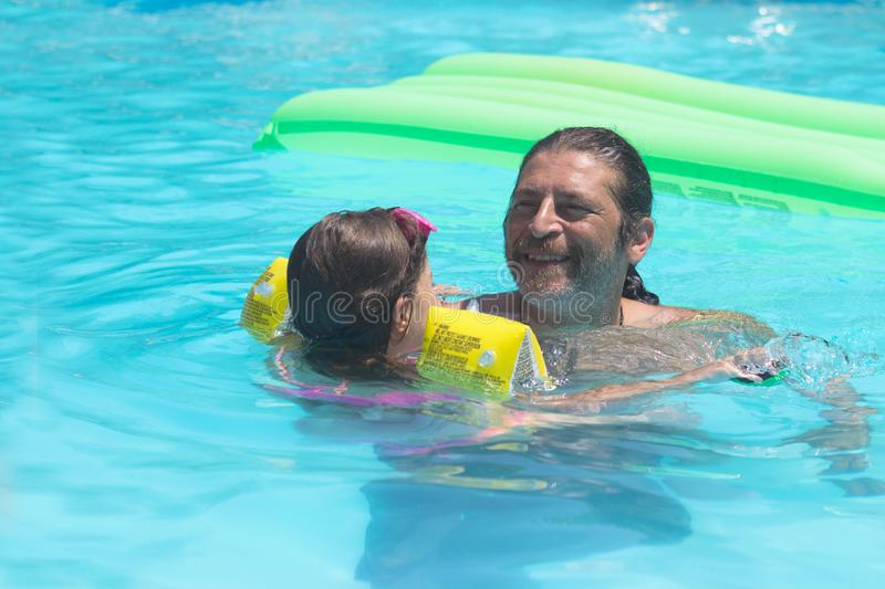 Happy father and daughter playing in the swimming pool; summertime. Background royalty free stock photography