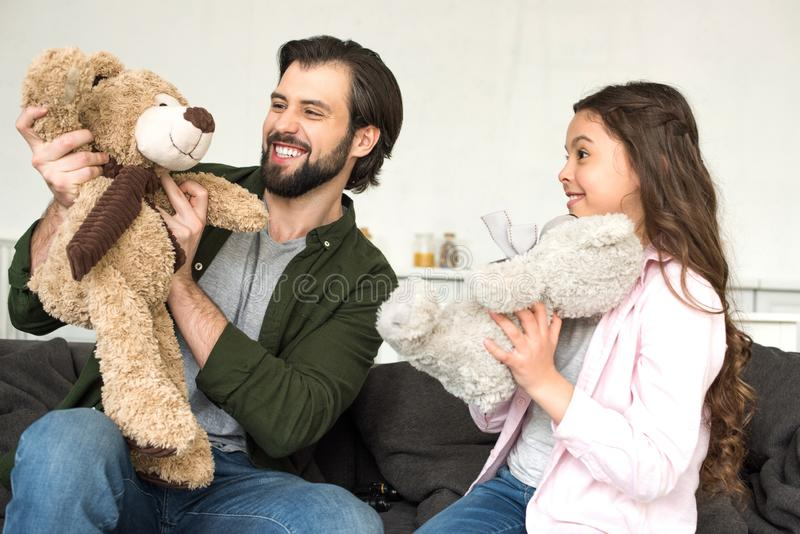 Happy father and daughter playing with teddy bears. At home stock photo