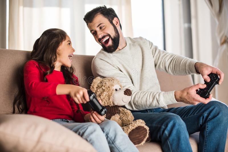 happy father and daughter playing video game at home and looking stock photography