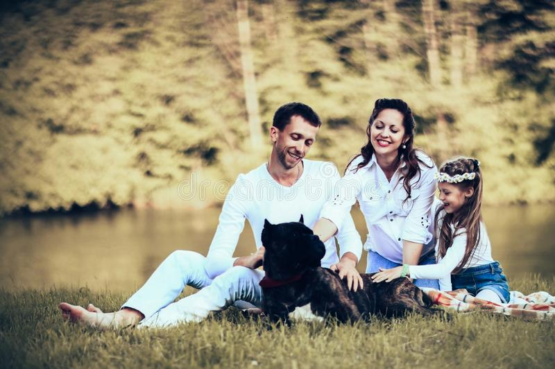Happy father of a daughter and a pregnant mom at a picnic. Happy father of a daughter and a pregnant mom in the picnic stock images