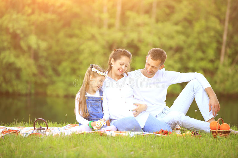 Happy father of a daughter and a pregnant mom at a picnic. Happy father and daughter pregnant mother on a picnic on a background of lake royalty free stock image