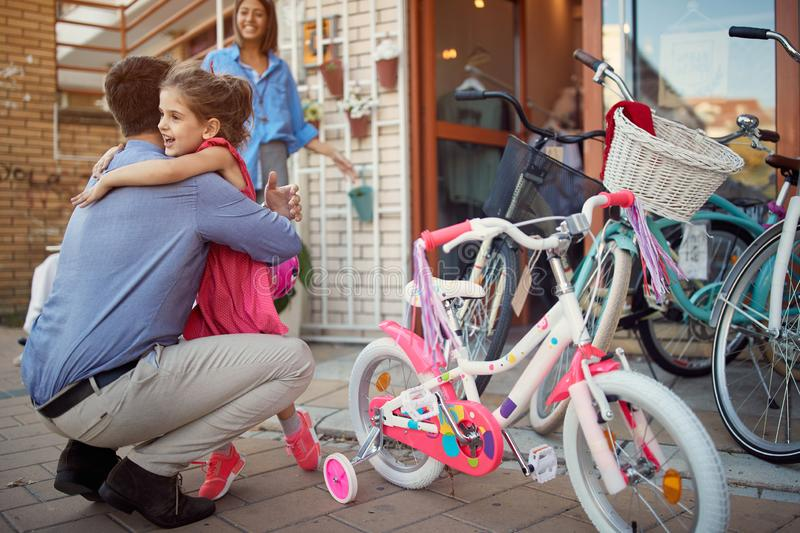 Father and daughter shopping new bicycle in bike shop. Happy father and daughter shopping new bicycle in bike shop royalty free stock photos