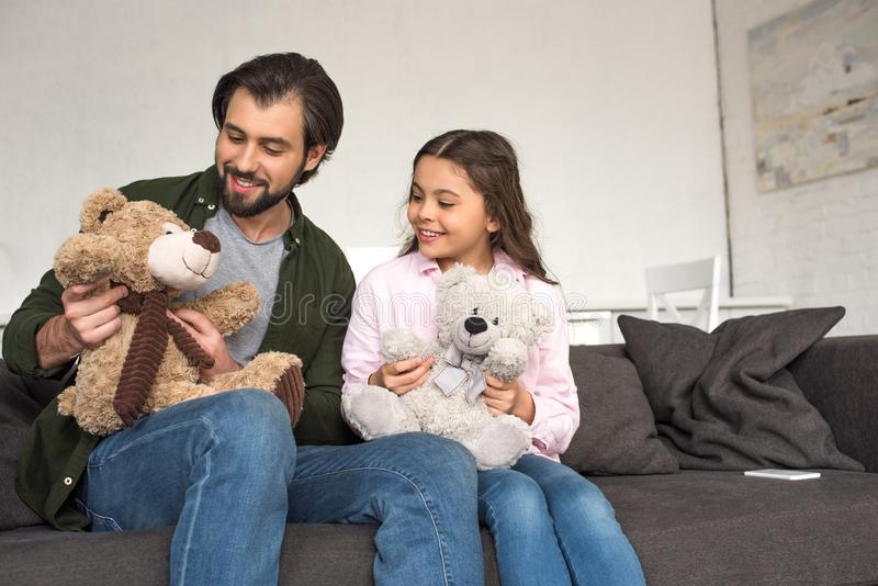 Happy father and daughter sitting on sofa and playing with teddy bears at home royalty free stock photos
