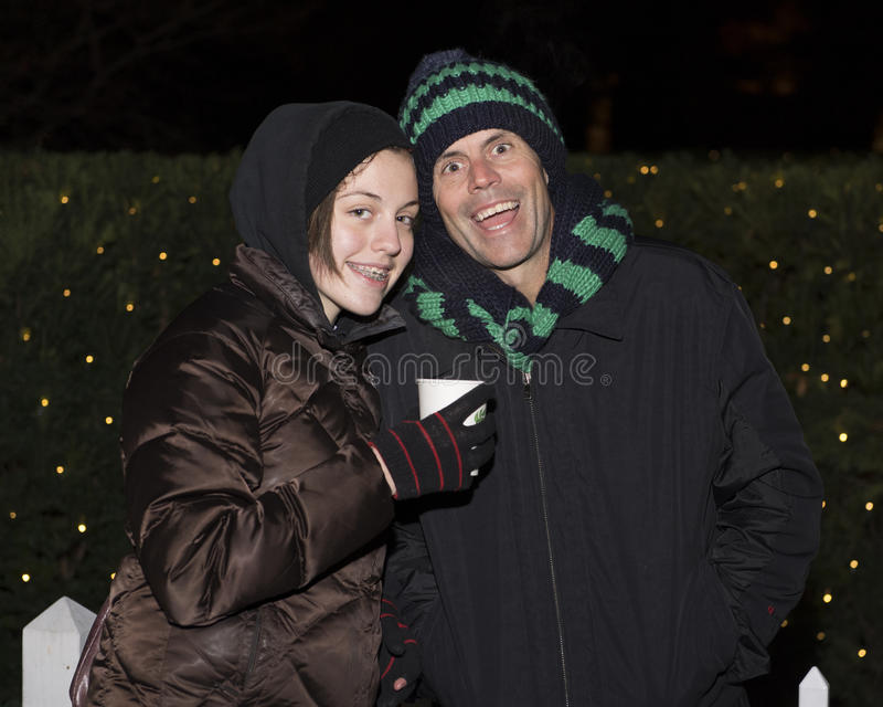 Happy father and daughter standing in the cold in front of bushes with Christmas lights stock photo