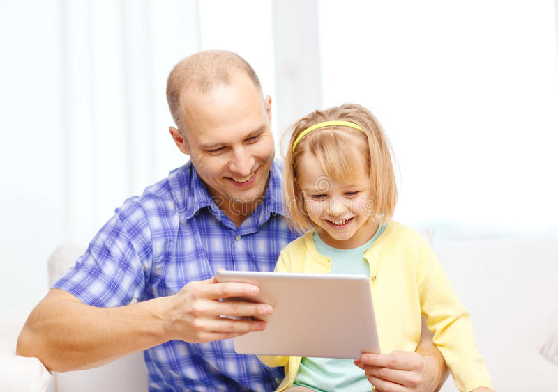 Happy father and daughter with tablet pc computer. Family, children, parenthood, technology and internet concept - happy father and daughter with tablet pc stock photo