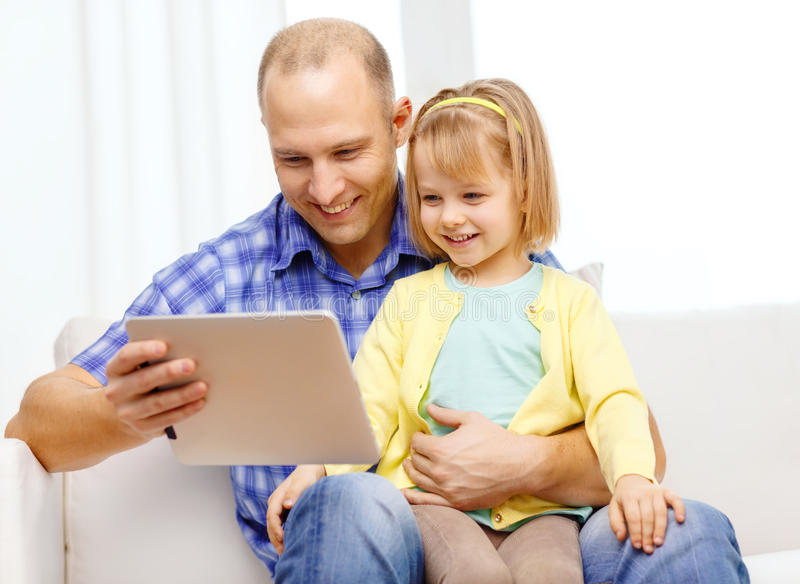 Happy father and daughter with tablet pc computer. Family, children, parenthood, technology and internet concept - happy father and daughter with tablet pc royalty free stock photography