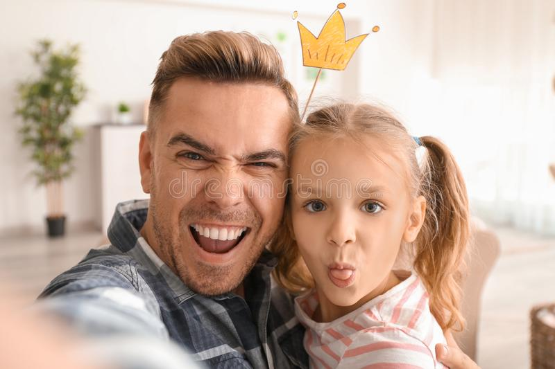Happy father and daughter taking funny selfie at home stock images