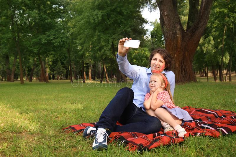 Happy father with daughter taking selfie while resting on plaid in park stock photo