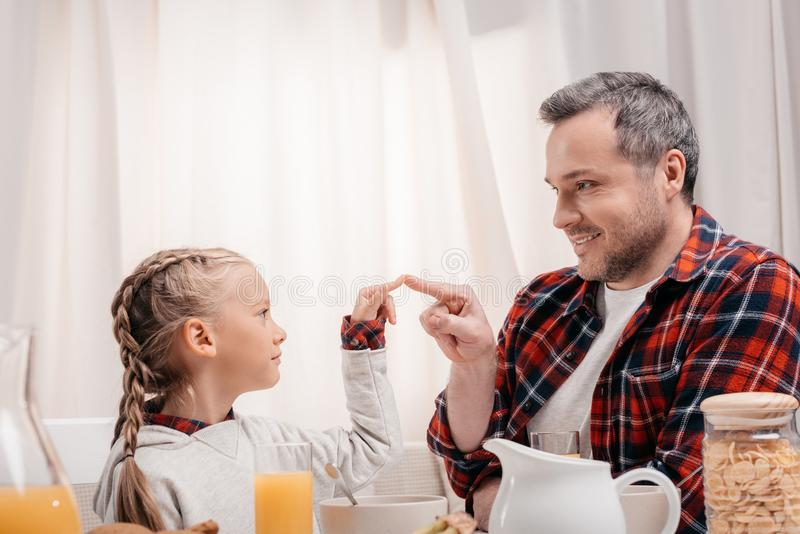 Happy father and daughter touching fingers while having. Breakfast together stock photography