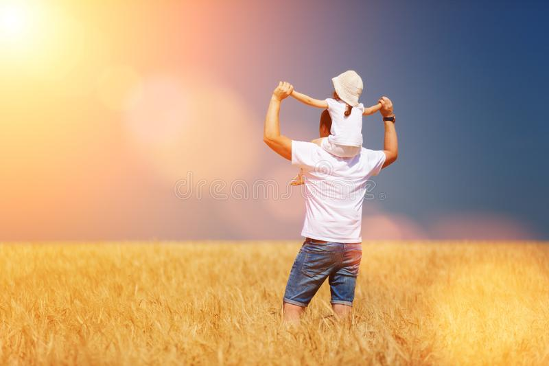 Happy father and daughter walk in the summer field. Nature beauty, blue sky and field with golden wheat. Outdoor lifestyle. royalty free stock photo