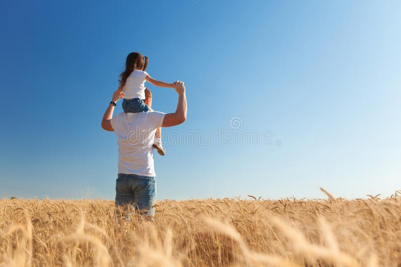Happy father and daughter walk in the summer field. Nature beauty, blue sky and field with golden wheat. Outdoor lifestyle. stock image