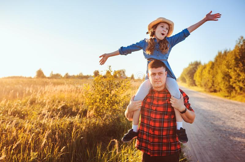 Happy father and daughter walking on summer meadow, having fun and playing. stock image