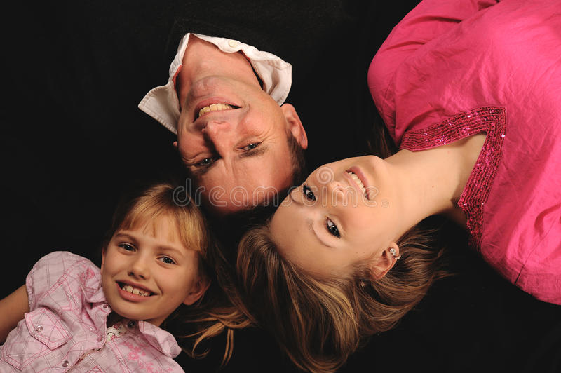 Happy father with daughters. Overhead view of happy father with teenage and young daughter; lying with heads together on black background royalty free stock photo