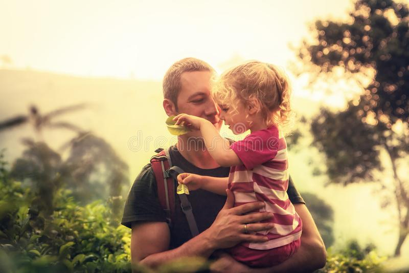 Happy father embracing child daughter outdoors with sunlight in the mountains during vacation as family travelling lifestyle stock photography