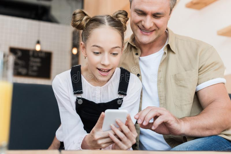 Father and daughter looking at smartphone stock image